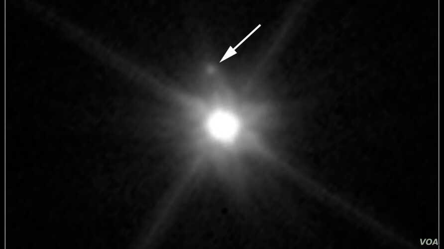 A newly discovered moon is seen orbiting the dwarf planet Makemake. (Hubblesite.org)
