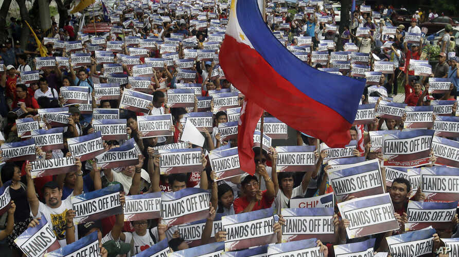 Protesters carry placards as they march in a Philippines Independence Day rally toward the Chinese Consulate in the financial district of Makati city east of Manila, Philippines, June 12, 2015.