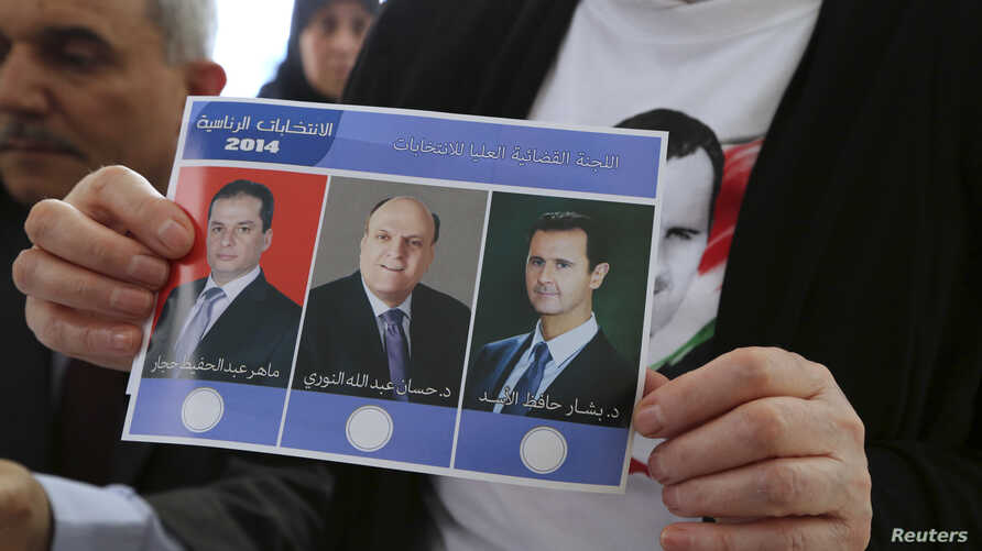 A Syrian national living in Beirut holds a ballot paper with pictures of the three presidential candidates, (from L-R) Maher Abdul-Hafiz Hajjar, Hassan Abdallah al-Nouri and Syria's President Bashar al-Assad, as she casts her vote ahead of the June 3