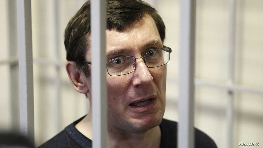 Ukraine's former interior minister Yuri Lutsenko looks out from defendant's cage during a court session in Kiev Feb. 27, 2012