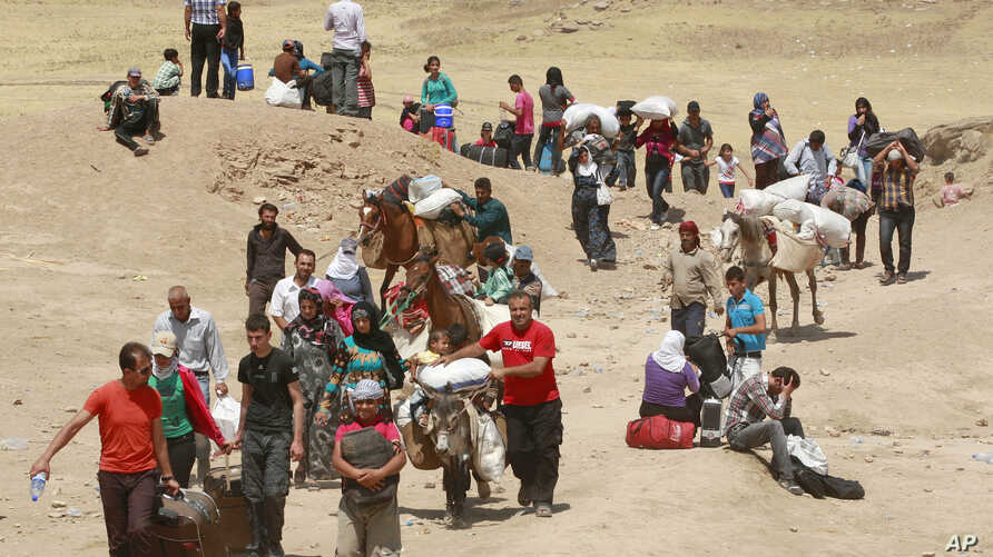 Syrian refugees cross into Iraq at the Peshkhabour border point in Dahuk, 260 miles (430 kilometers) northwest of Baghdad, Iraq,  August 20, 2013.