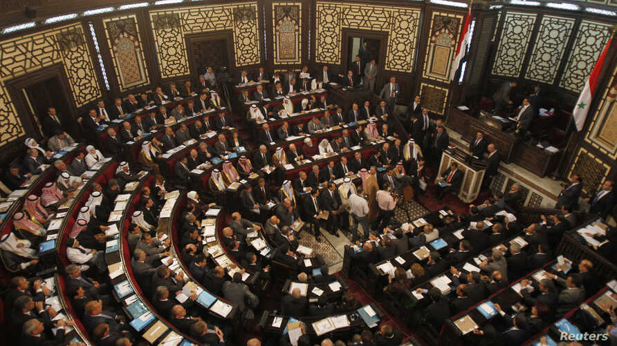 FILE - Newly elected members of Syria's parliament attend the first parlimentary session of the new constitution in Damascus, May 24, 2012.