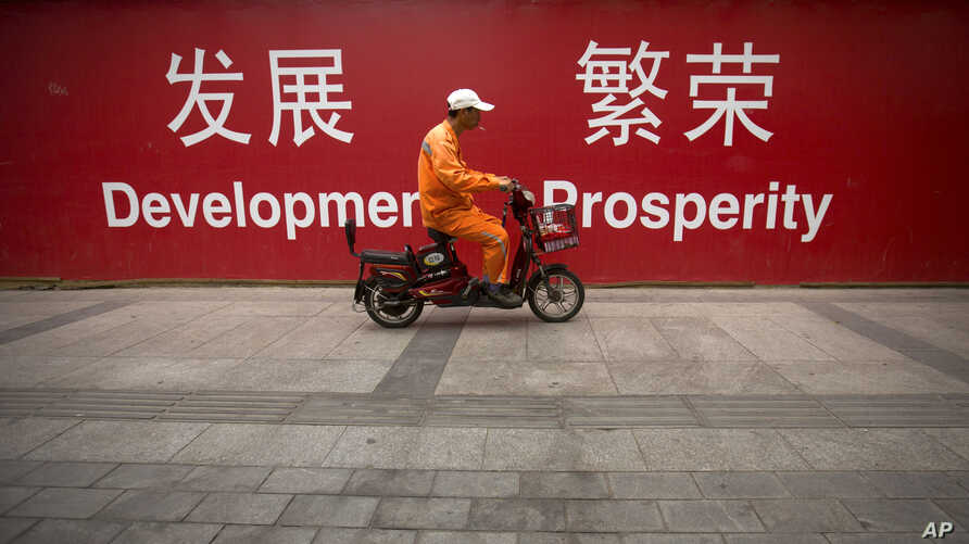 """FILE - A maintenance worker rides a scooter past banners reading """"Development"""" and """"Prosperity"""" in English and Chinese on a street in central Beijing, July 15, 2015."""