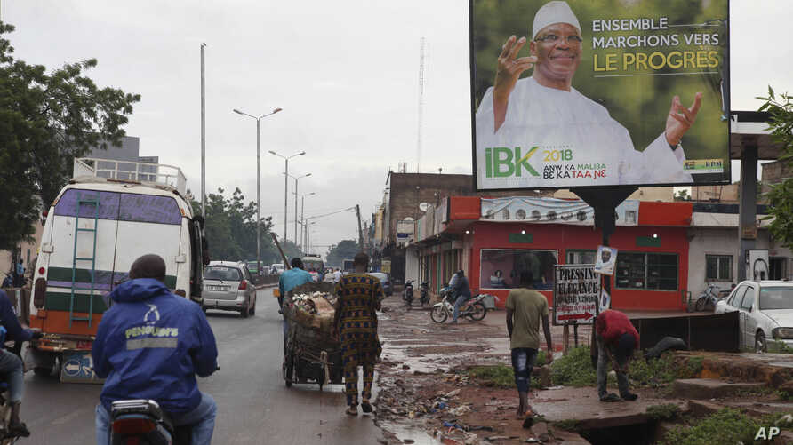 """FILE - Motorbike taxis ride past a giant billboard of Mali's incumbent president, Ibrahim Boubacar Keita, that reads """"the great Mali advance"""" in Bamako, Mali, July 18, 2018. As deadly attacks by extremists become more brazen in Mali, officials and ci"""