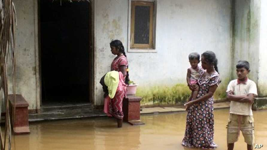 A family stands near their flooded home in Batticaloa district, about 320 km (199 miles) east of Colombo, February 6, 2011.