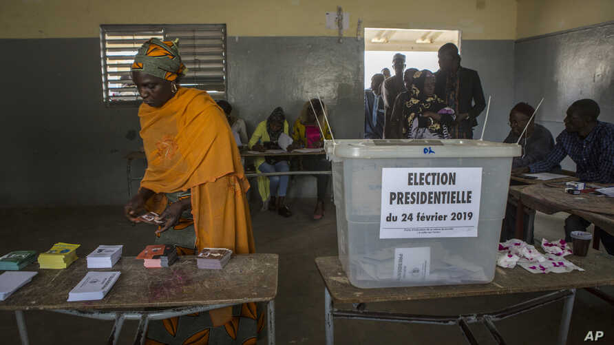 A Senegalese woman picks up voting cards before casting her ballot at a polling station in Dakar, Senegal, Sunday Feb. 24, 2019.