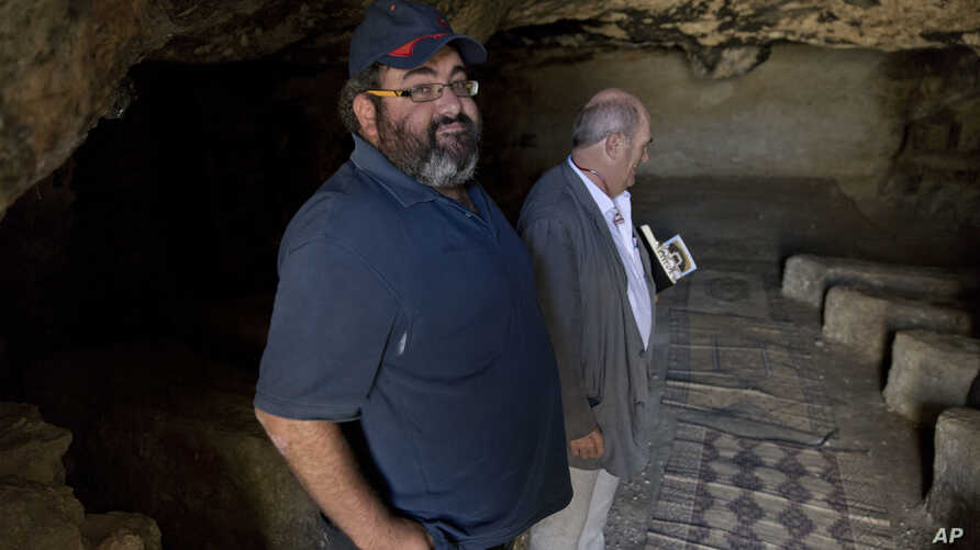 Yehuda Shaul, front, co-founder of Breaking The Silence, and Irish author Colm Toibin visit Susiya archaeological park, south of Hebron, West Bank, July 12, 2016.