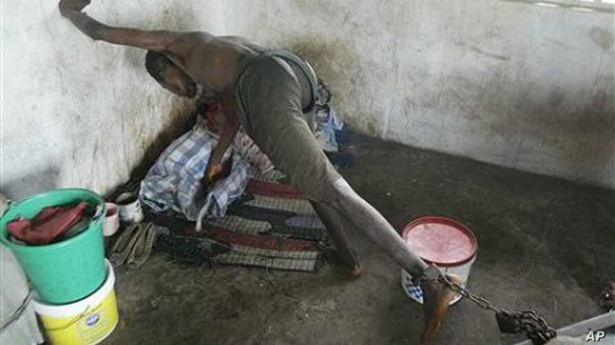 A patient from the Holy Ghost Mental Home tries to reach out, whilst chained to his bed, in Monrovia, Liberia (File Photo)