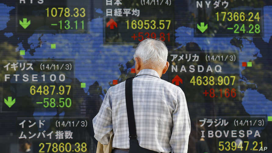 A man looks at an electronic stock board of a securities firm in Tokyo, Nov. 4, 2014.
