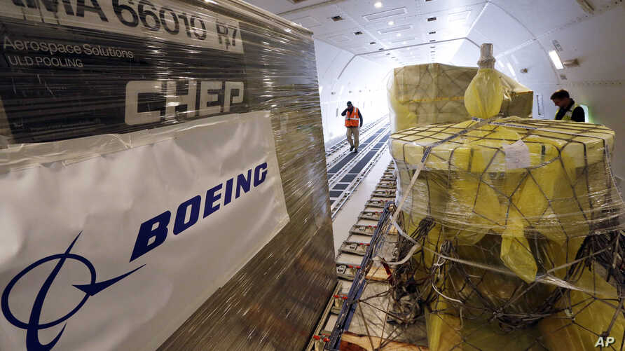 FILE - Workers move cargo into position inside a new AirBridgeCargo Boeing 787-8 freighter airplane, Oct. 7, 2016, at Seattle-Tacoma International Airport.