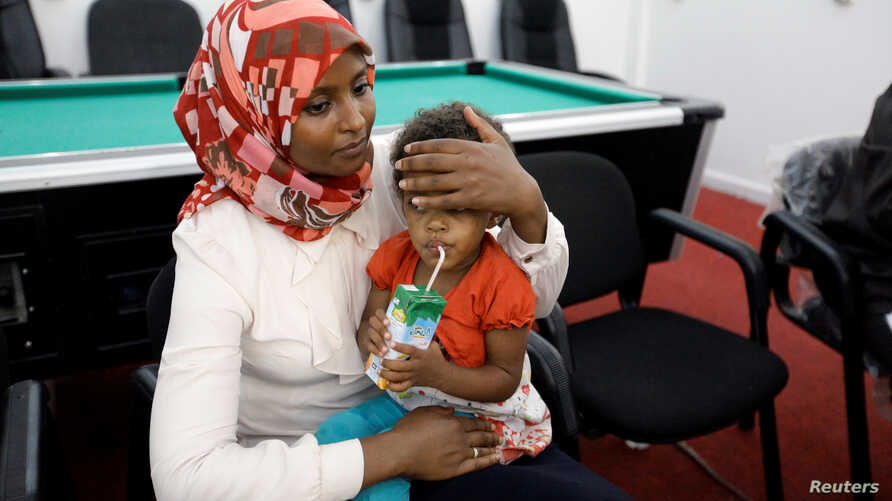 A Sudanese official holds a child of Sudanese Islamic State members who operated in Libya, after Libyan Red Crescent handed them over, in Misrata, Libya August 20, 2017.
