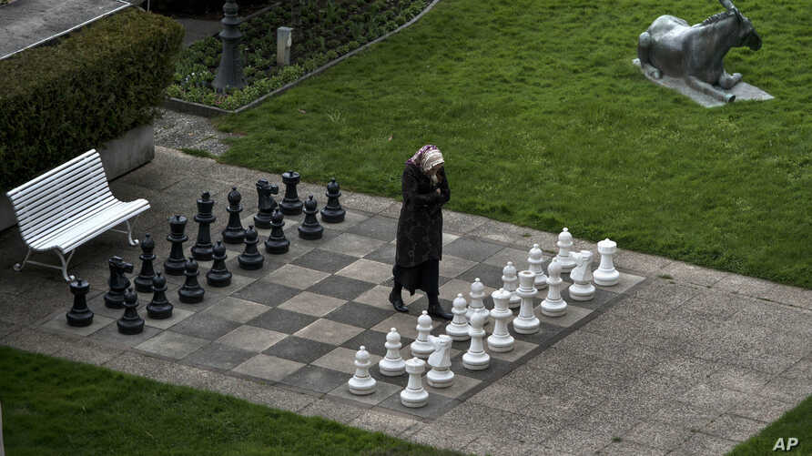 A member of the Iranian media walks on an open air chess board at the site of negotiations about Iran's nuclear program, between Iran officials and representatives of the world powers, Monday March 30, 2015 in Lausanne, Switzerland.