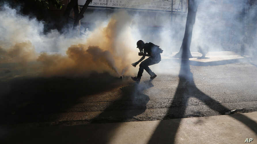 A protester retrieves a tear gas canister from security forces blocking an opposition march from reaching the National Electoral Council headquarters in Caracas, Venezuela, May 24, 2017.