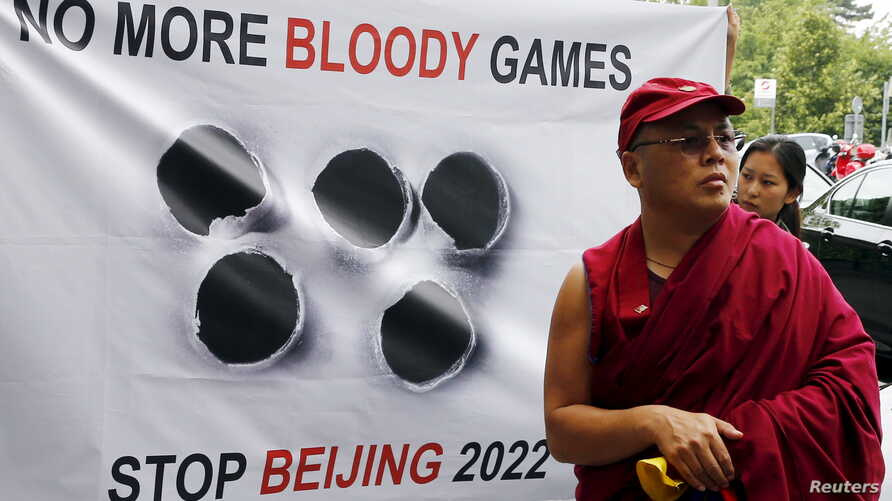 FILE - A Tibetan monk stands in front of a banner outside the Beijing 2022 Winter Olympic Games Bid presentation at the Palace Hotel in Lausanne, Switzerland June 10, 2015.