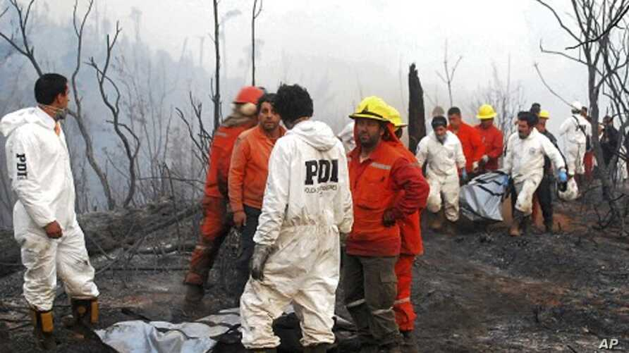 Rescue team members carry the body of a firefighter after a forest fire near Temuco city, south of Santiago, January 5, 2012.