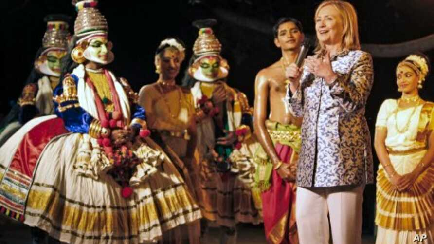 U.S. Secretary of State Hillary Rodham Clinton, second right, shows appreciation after watching a performance by the Indian classical dancers at Kalakshetra in Chennai, India, July 20, 2011