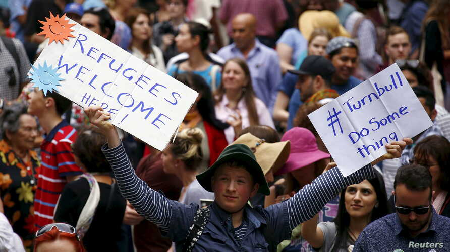 FILE - Demonstrators hold aloft placards during a rally in support of refugees that was part of a national campaign in central Sydney, Australia, Oct. 11, 2015.