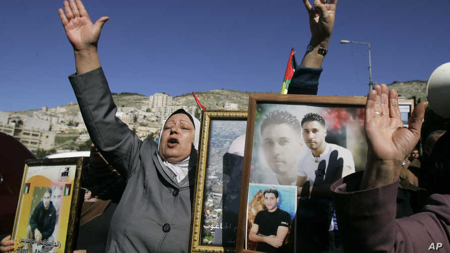 Palestinian women hold pictures of prisoners jailed in Israel during a rally calling for their release, in the West Bank city of Nablus, February 4, 2013.