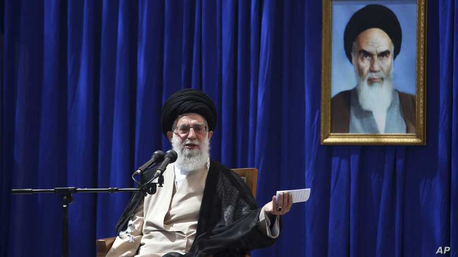 Iranian supreme leader Ayatollah Ali Khamenei delivers a speech, during a ceremony marking the 23rd death anniversary of the late revolutionary founder Ayatollah Khomeini, shown in the poster at right, at his mausoleum, just outside Tehran, Iran, Jun