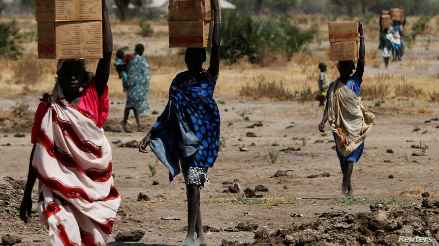 Women carry boxes of nutritional food delivered by the United Nations World Food Program, in Rubkuai, South Sudan, Feb. 16, 2017.