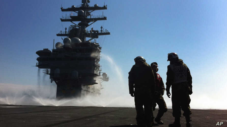 March 23: U.S. Navy deck crew stand near the island on the deck sprayed for radioactive decontamination aboard USS Ronald Reagan  off the Japanese coast. (AP Photo/Eugene Hoshiko)