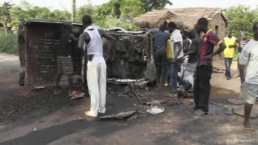 People gather around a burnt Seleka Rebel truck in Begoua, 17 km (10 miles) from capital Bangui, in this still image taken from video, Mar. 23, 2013.
