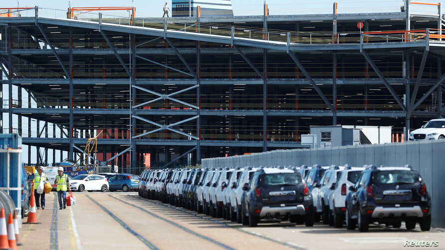 Cars readied for export are parked next to a vehicle storage facility on the dockside at the ABP port in Southampton, Britain, Aug. 16, 2017.