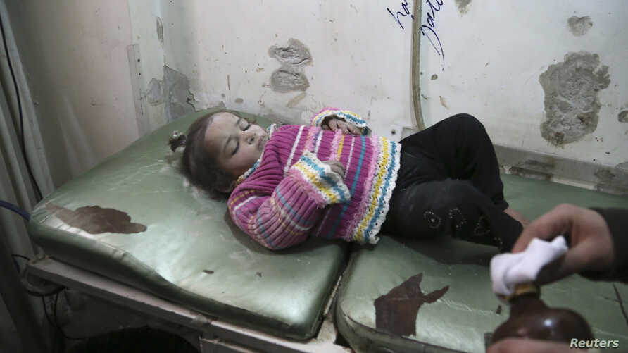 FILE - An injured girl lies in a field hospital bed in Aleppo, Syria, December 28, 2013.