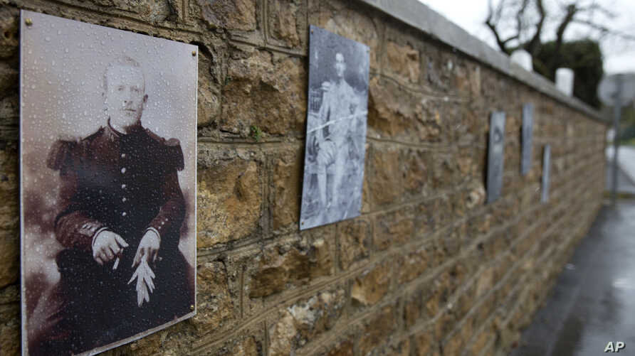 A photo of French WWI soldier Augustin Trebuchon, taken Oct. 30, 2018, hangs on a wall outside a cemetery in Vrigne-Meuse, France.