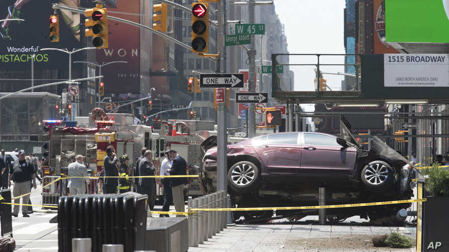 A car rests on a security barrier in New York's Times Square after driving through a crowd of pedestrians, injuring at least a dozen people, May 18, 2017.