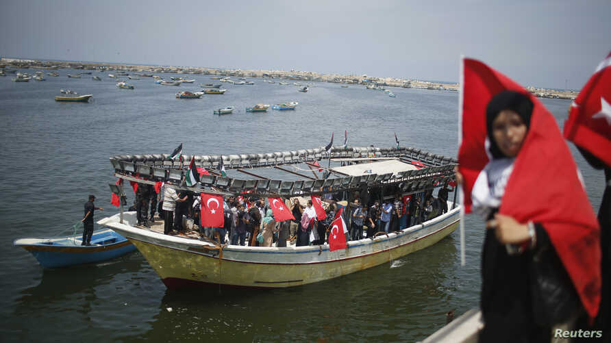 A Palestinian woman holds a Turkish flag as activists ride a boat during a rally ahead of the 4th anniversary of the Mavi Marmara Gaza flotilla incident, at the seaport of Gaza City May 29, 2014.