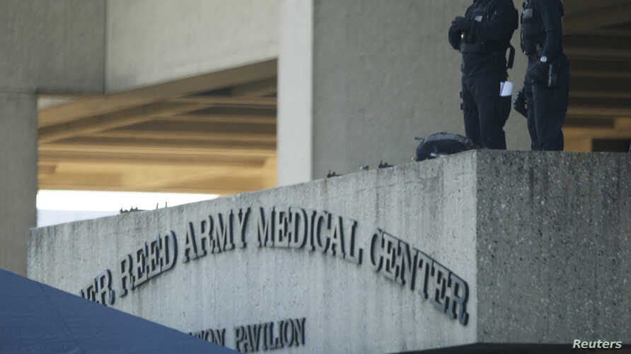 FILE - Security personnel keep an observation post on the roof to the entrance of the Walter Reed Army Medical Center in Washington, November 6, 2009.
