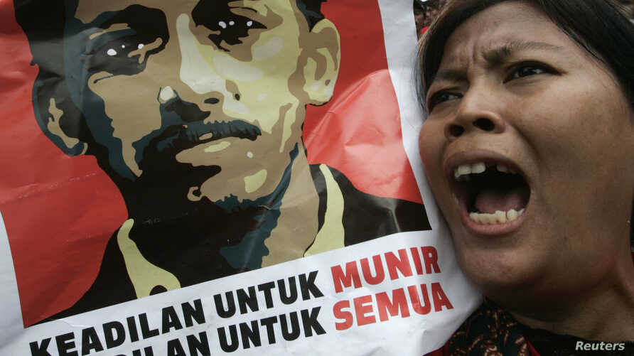 FILE - An Indonesian protester shouts slogans as she holds a poster of Munir Said Thalib during a demonstration outside the National Intelligence Agency (BIN) office in Jakarta.