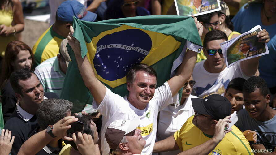FILE - Congressman Jair Bolsonaro holds a Brazilian flag during a protest against then-President Dilma Rousseff, in Brasilia, Brazil, March 13, 2016.