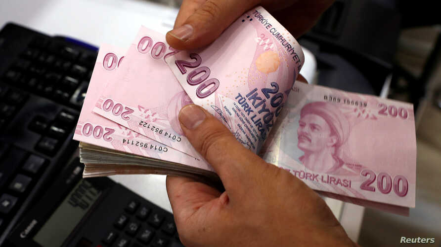 FILE - A money changer counts Turkish lira banknotes at a currency exchange office in Istanbul, Turkey, Aug. 2, 2018.