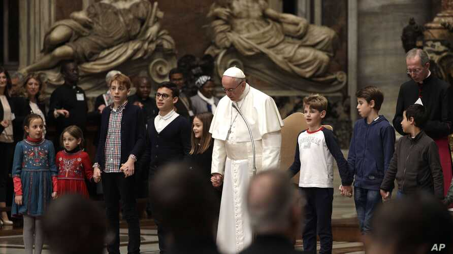 Pope Francis holds hands with children as he celebrates a prayer for peace in South Sudan and the Democratic Republic of the Congo, inside St. Peter's Basilica, at the Vatican, Nov. 23, 2017.