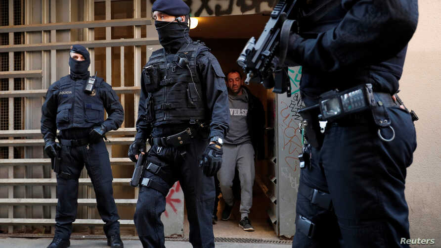 Mossos d'Esquadra police officers escort a detained suspect who allegedly had the intention of committing a terrorist attack in Barcelona, Spain, Jan. 15, 2019.