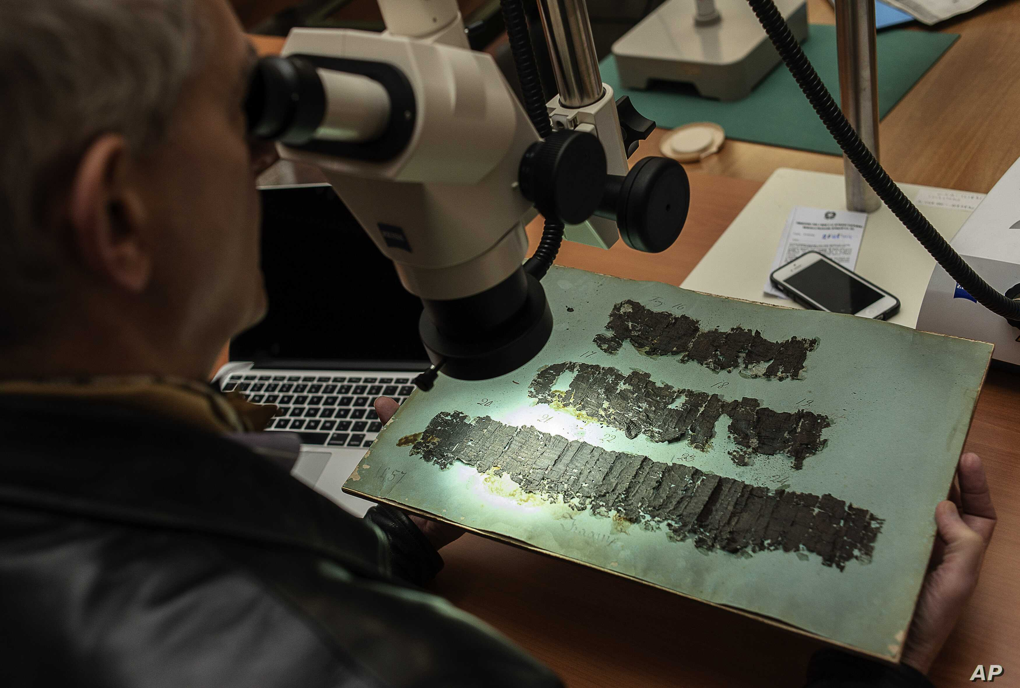 David Blank, a professor of classics at the University of California, looks through a microscope at an ancient papyrus at the Naples National Library in Italy, Jan. 20, 2015.