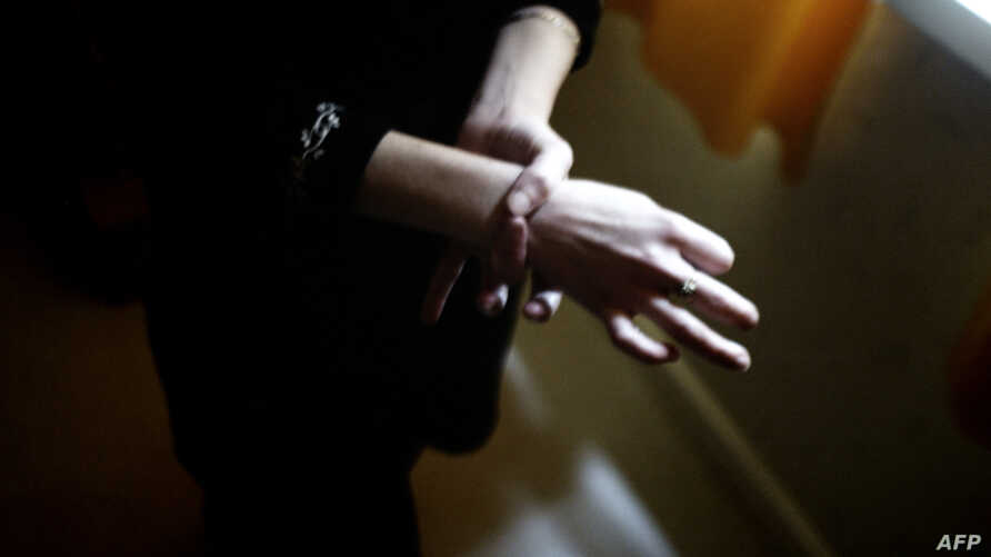 FILE - Helene, a 28-year-old woman, shows the size of her wrist as she stands in her apartment in Bourges, France. She had been diagnosed with anorexia 10 years before.