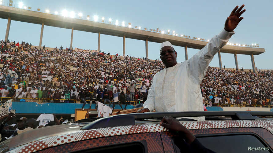FILE - Senegal's President and candidate for the upcoming presidential elections Macky Sall greets his supporters as he arrives to attend his final campaign rally in Dakar, Feb. 22, 2019.