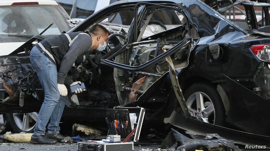 An investigator works near a car that was damaged by an explosion in central Kyiv, Ukraine, Sept. 8, 2017.