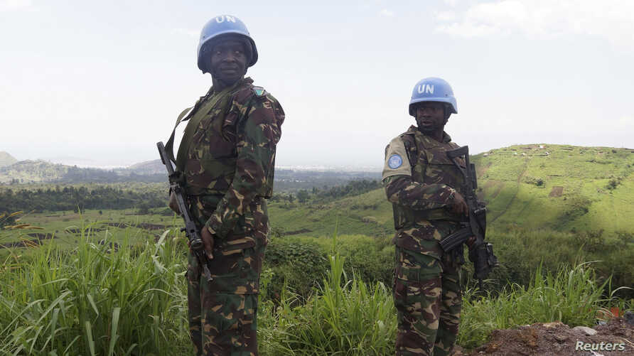 FILE - U.N. peacekeepers from Tanzania hold their weapons as they patrol outside Goma during a visit by officials from the U.N. Security Council in the eastern Democratic Republic of Congo, October 2013.