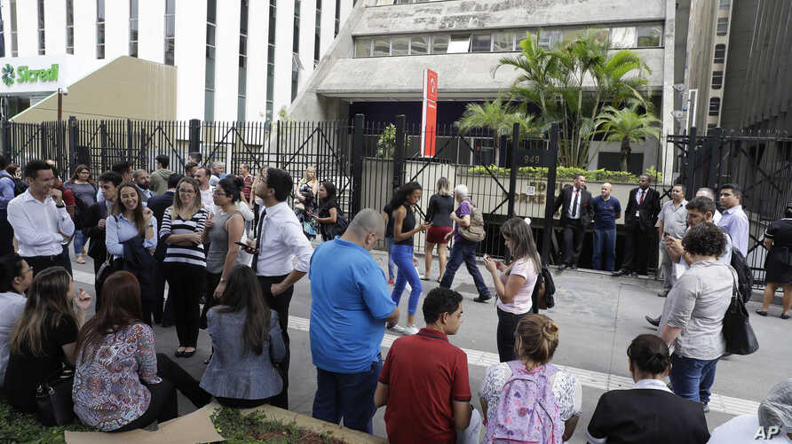People gather outside a building that was temporarily evacuated in Sao Paulo, Brazil, April 2, 2018, after a powerful 6.8-magnitude earthquake struck Bolivia.