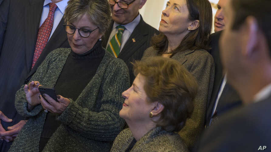Senate Environment and Public Works Committee Chairman Sen. Barbara Boxer, D-Calif., left, checks her phone during a meeting of the Senate Climate Action Task Force prior to taking to the Senate Floor all night to urge action on climate change, March