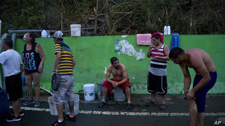 People affected by Hurricane Maria wait in line to collect water piped from a creek in the mountains, in Naranjito, Puerto Rico, Sept. 28, 2017. Residents of the area drive to the pipes to bathe because they were left without water by the damage caus