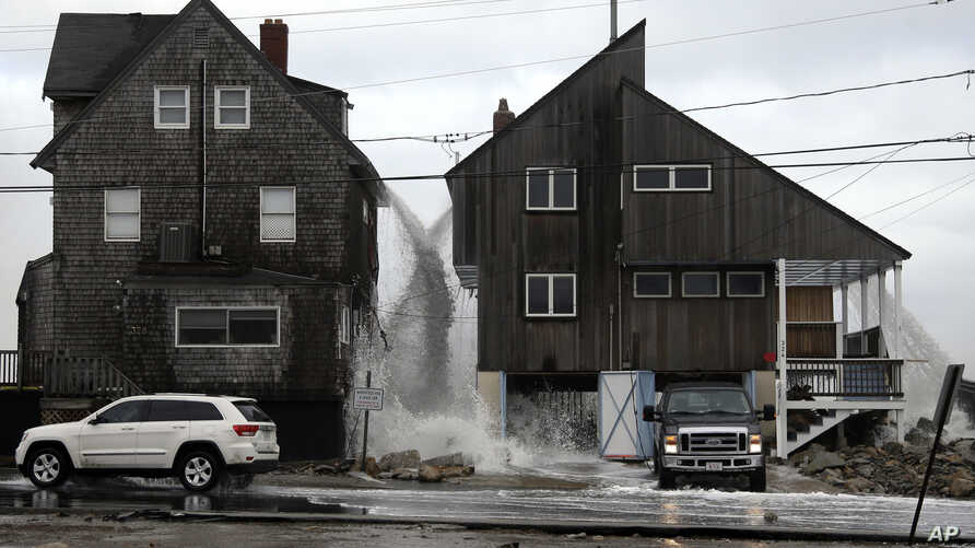 Ocean water pours off the roofs of these beachfront homes, March 6, 2018, as high surf continues in Marshfield, Massachusetts.