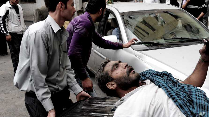This photo released by the Syrian official news agency SANA shows a Syrian man helping an injured man at the scene after a blast in Damascus, Syria, November 5, 2012.