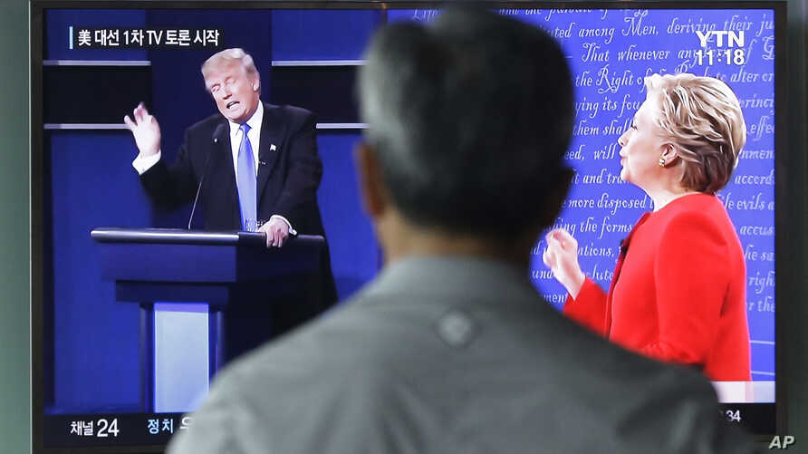 A man watches a TV screen showing the live broadcast of the U.S. presidential debate between Democratic presidential candidate Hillary Clinton and Republican presidential candidate Donald Trump, at Seoul Railway Station in Seoul, South Korea, Sept. 2