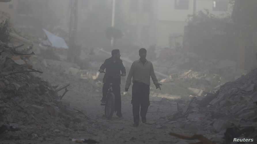 Men walk past damage that was reportedly caused by shelling from Syrian government forces, along a street in the Duma neighborhood of Damascus, Nov. 17, 2013.