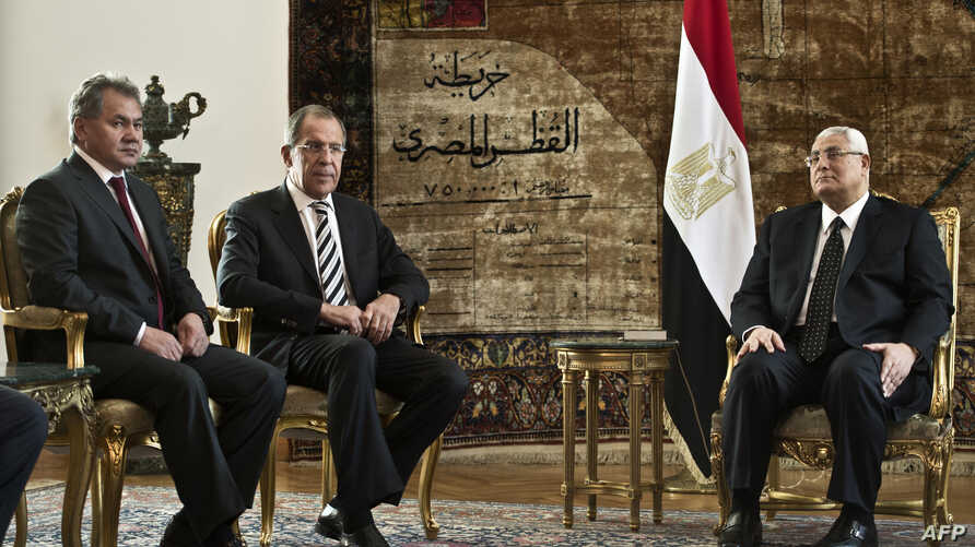 Egypt's interim president Adly Mansour (R) meets with Russ